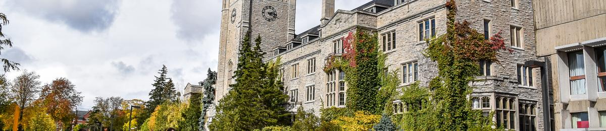 Johnston Hall, an iconic University of Guelph stone building, surrounded by trees starting to show fall foliage.