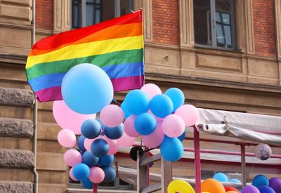 Balloons and flags fly at Pride celebration. The balloons are trans-colours, pink and blue. The flag is the Pride flag.